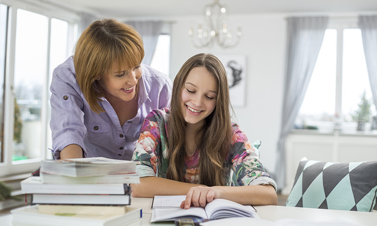 Smiling mother assisting daughter in doing homework at table