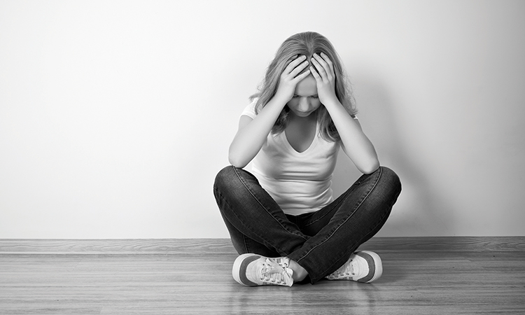 girl sits in a depression on the floor near the wall monochrome